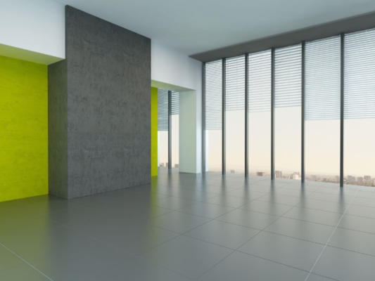 Interior architectural background of a large empty room with yellow wall accents and floor-to-ceiling panoramic windows reflecting on a grey floor